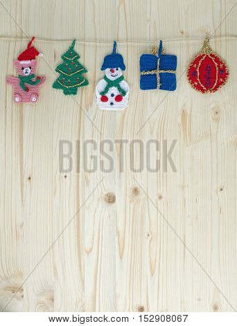 Several crocheted christmas hangers on a cord on wood, background