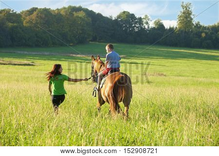 Horseback Riding Lessons - Woman Leading a Horse with a Boy in Saddle