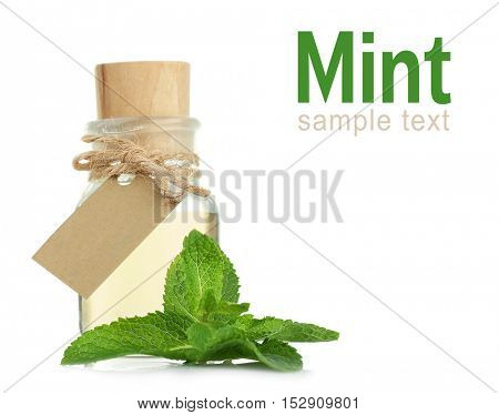 Glass bottle of essential oil, closeup. Word MINT on white background. Spa beauty concept.
