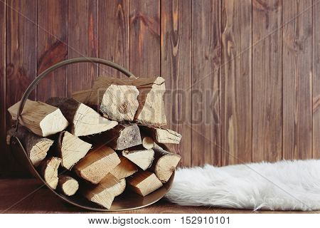 Basket with firewood on wooden background