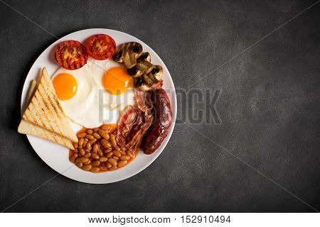 English breakfast prepared with two fried eggs, beans in tomato sauce, grilled tomatoes, mushrooms, bacon and toasts. Close up