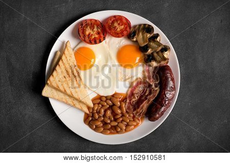 English breakfast prepared with two fried eggs, beans in tomato sauce, grilled tomatoes, mushrooms, bacon and toasts. Black background