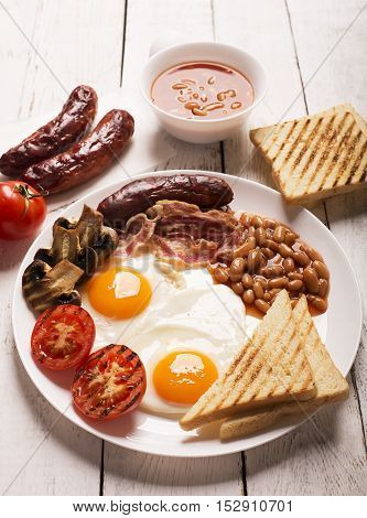 English breakfast prepared with two fried eggs, beans in tomato sauce, grilled tomatoes, mushrooms, bacon and toasts on a white rustic table. Vertical orientation