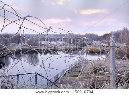Post a fence of barbed wire in winter in frost at dawn.