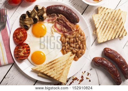 English breakfast prepared with two fried eggs, beans in tomato sauce, grilled tomatoes, mushrooms, bacon and toasts. Meal on a white wooden table, top view