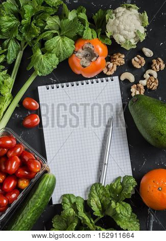 Food background. Fresh vegetables fruits and blank notepad on a dark background. Concept of healthy eating diet and planning