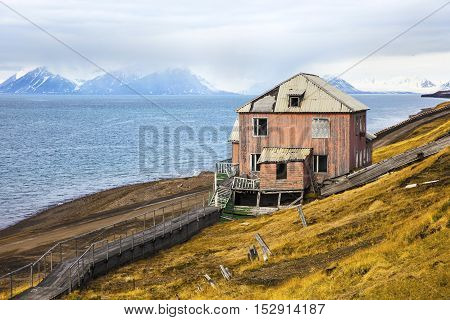 Abandoned house in Barentsburg settlement. Clouds over mountains covered with snow in the cold arctic environment at Svalbard.