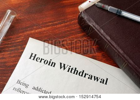 Heroin withdrawal written on a paper. Drug addiction concept.