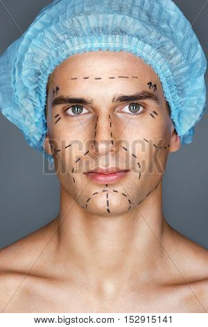 Beautiful man in medical hat with pencil marks on skin for cosmetic medical procedures ready for operation. Beauty Face
