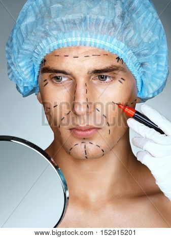 Attractive man patient in medical hat look in the mirror while the nurse deals surgical mark lines on eyes nose cheek and jaw. Beauty face concept
