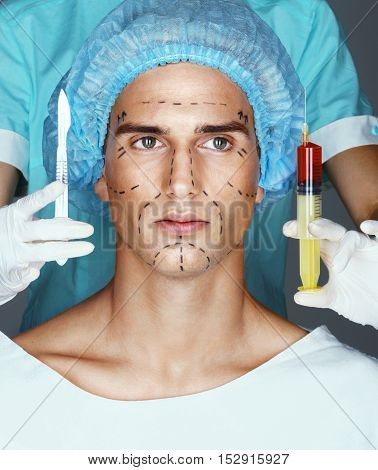 Nurse with syringe and scalpel near the face of the patient. Attractive of male in medical headwear with pencil marks on skin for cosmetic medical procedures.