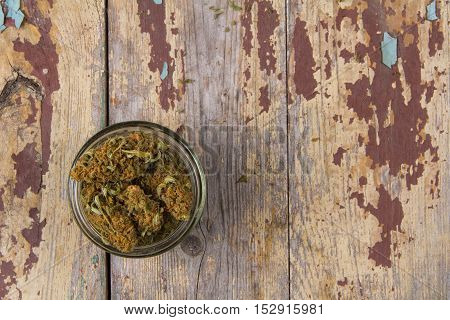 Marijuana buds in the glass pot on the rustic wooden table