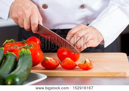 Chef cutting some delicious and healthy red tomatoes