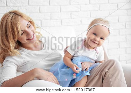 Mother with daughter sitting in armchair on white brick wall background