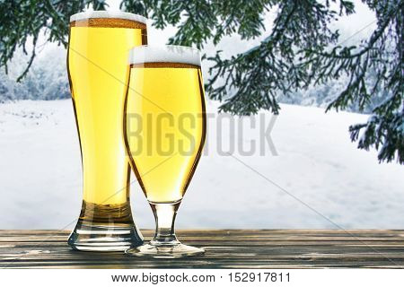 Glasses of beer on wooden table against winter nature background.