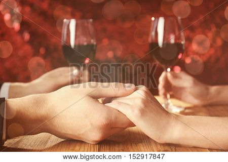 Young couple holding hands together at restaurant
