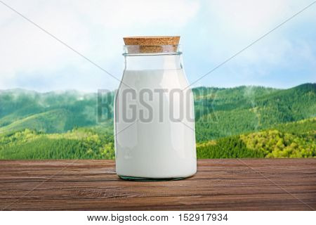 Glass bottle of milk on wooden table against blurred landscape background. Dairy concept.