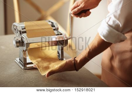 Man using pasta machine to prepare dough for tagliatelle, close up view