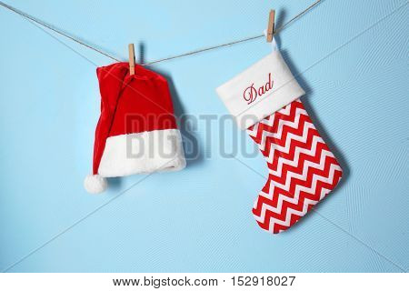Christmas stocking and Santa Claus hat hanging against blue background