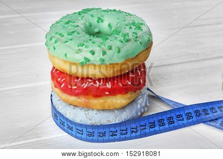 Dieting concept. Pile of tasty doughnuts and measuring tape on white table
