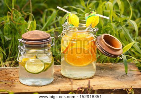 Orange and lemon lemonade in pitchers and glasses on wooden table on natural background