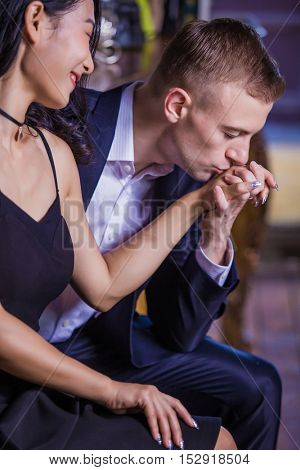 Seductive man kissing his wifes hand before they go to the bedroom