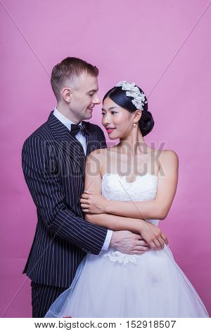 Loving bride and groom holding each other while standing against pink background