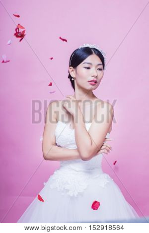 Portrait of beautiful Chinese bride against pink background