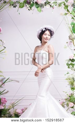 Portrait of elegant bride standing against grey wall with flowers surrounding it