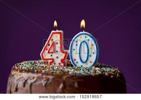 Birthday cake with burning candles on dark background