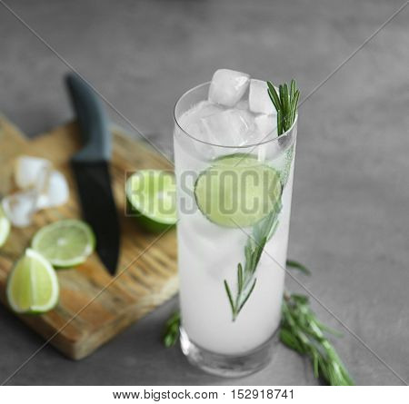 Glass of cocktail with ice on grey background