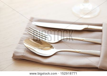 Fork, spoon and knife on linen napkin