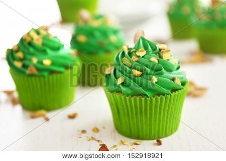 Green pistachio cupcakes on wooden table