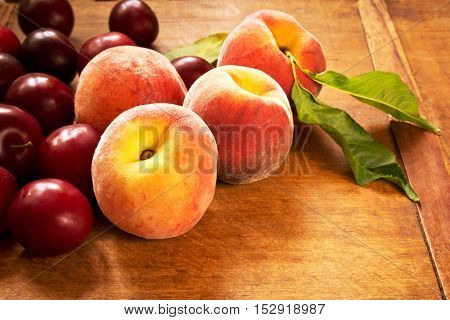 Fresh juicy peaches and plums on the kitchen table