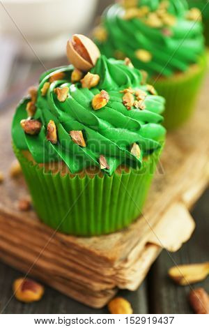 Green pistachio cupcake with book on wooden background