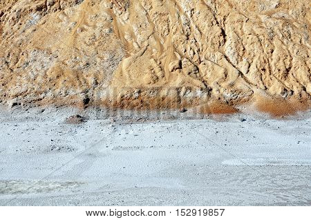 The surface covered with white salt layer a pile of yellow sand texture. Industrial background with space for text.