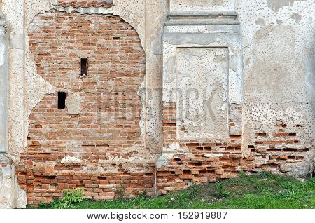 Brick wall of an old building with peeling plaster and traces of bullet holes.