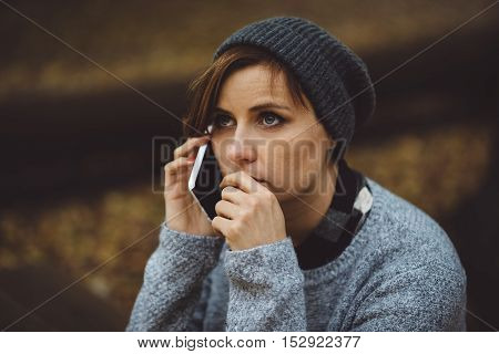 Portrait of sad, depressed woman sitting alone in the forest with smartphone. Solitude or depression concept. Millenial dealing with problems and emotions.