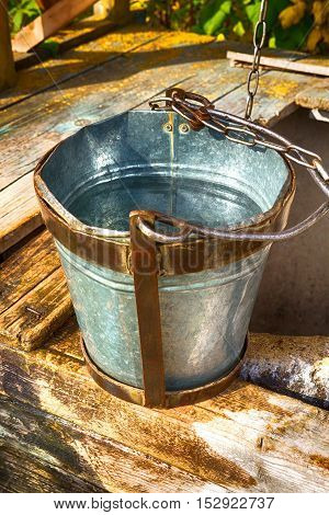 Old rustic wooden well and bucket on an iron chain