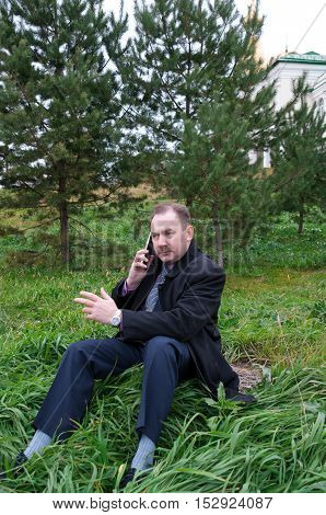 Man talking on the phone gesturing hand on nature