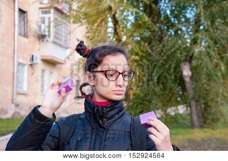 The girl in glasses looks into the open lilac box