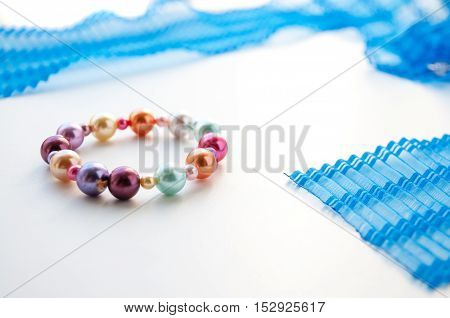 Bracelet of colored pearls lies next to a blue ribbon