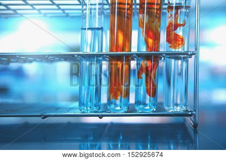 four test tubes with orange solution in lab blue science background