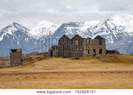 Abandoned house in Iceland near large mountains