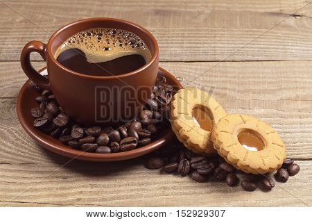 Cup of hot coffee with cookies on wooden background