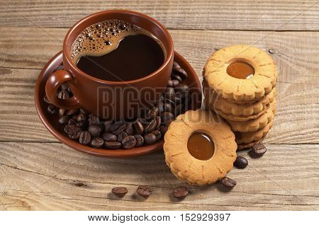 Cup of hot coffee and stack of cookies on wooden background