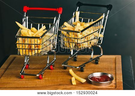 Fresh Fried French Fries With Ketchup On Wooden Background. Original Serving In A Small Iron Cart