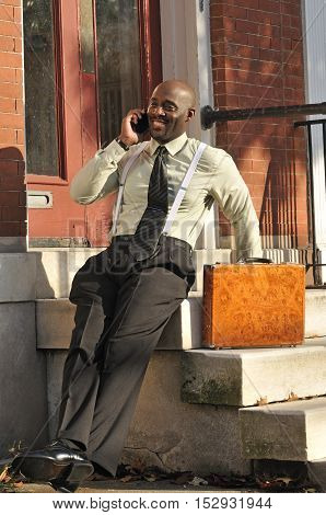 Happy African American businessman speaking on phone in the city