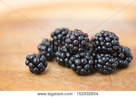 Ripe blackberries on wooden cutting board close up