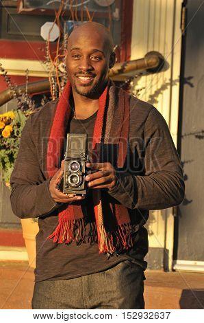 Male photographer using vintage camera to take photos